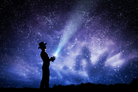 stars night: Man in hat throwing light beam up the night sky full of stars. Conceptual - explore, dream, magic, fantasy.