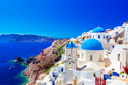 Oia town on Santorini island, Greece. Traditional and famous houses and churches with blue domes over the Caldera, Aegean sea 스톡 콘텐츠