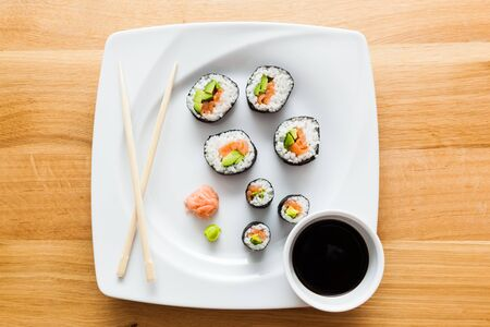 sushi plate: Sushi with salmon, avocado, rice in seaweed and chopsticks served on a plate with wasabi and ginger. Japanese, Asian healthy food. View from the top. Stock Photo