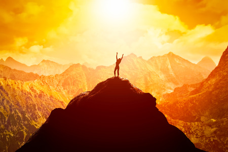 Mujer feliz con las manos arriba en el pico de la montaña disfrutando del éxito, la libertad y el futuro brillante.