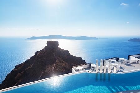 Pool mit Blick auf die Caldera über der Ägäis, Santorini, Griechenland an heißen, sonnigen Sommertag.