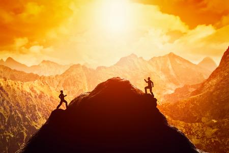 Dos hombres corriendo carrera hacia la cima de la montaña. La competencia, los rivales, reto en conceptos de vida