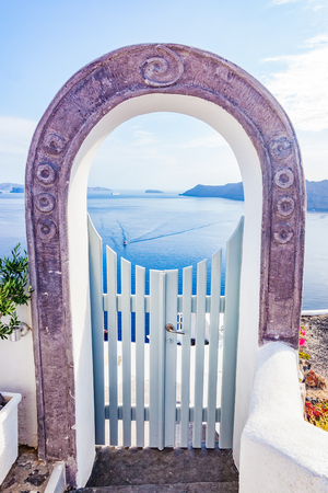 thera: Traditional fence gate in Oia on Santorini island, Greece. Aegean sea and Caldera in the background. Blue sky, travel, vacation time.