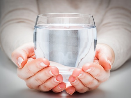 A glass of clean mineral water in womans hands. Concept of environment protection, healthy drink. Imagens