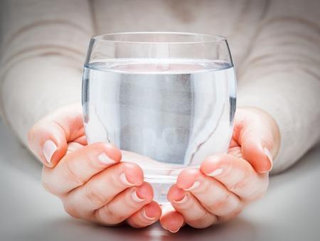 vaso de agua: Un vaso de agua mineral limpio en manos de la mujer. Concepto de protección del medio ambiente, una bebida saludable. Foto de archivo