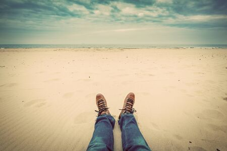 First person perspective of man legs in jeans on the autumn beach. Vintage, retro style Stock Photo