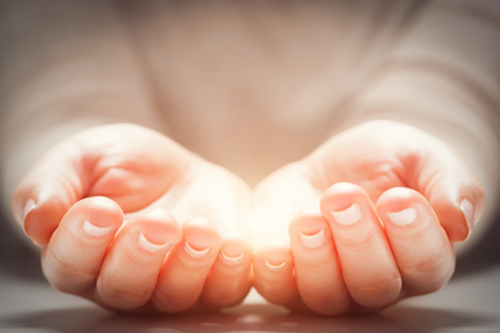 Light in woman's hands. Concepts of sharing, giving, offering, new life Standard-Bild