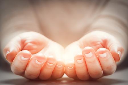 Luz en manos de la mujer. Los conceptos de compartir, dar, ofrecer, nueva vida Foto de archivo - 56766617
