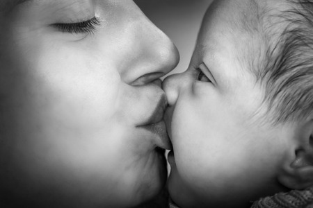 fondness: Mother kissing her newborn baby. Close-up portrait, black and white Stock Photo