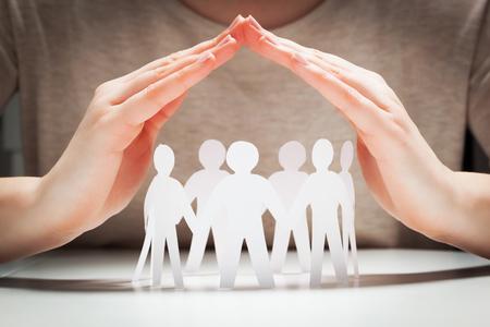 Papier Menschen, die unter den Händen in der Geste des Schutzes. Konzept der Versicherung, sozialer Schutz und Unterstützung. Standard-Bild