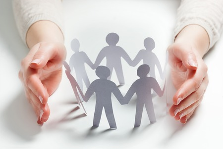 Paper people surrounded by hands in gesture of protection. Concept of insurance, social protection and support. Archivio Fotografico