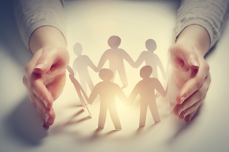 Paper people surrounded by hands in gesture of protection. Concept of insurance, social protection and support. Stockfoto