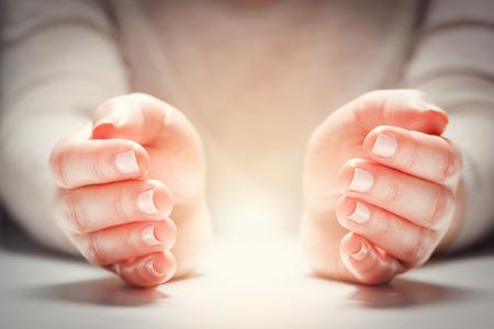 Licht zwischen den Händen der Frau in der Geste des Schutzes, der Pflege. Konzept Versicherung, Sicherheit und Schaffung Standard-Bild