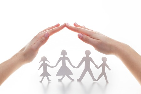 protection hands: Paper family under hands in gesture of protection. Concept of insurance, family protection and support.