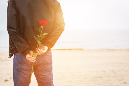 romantic date: Man with a rose behind his back waiting for love. Date on the beach. Romantic surprise Stock Photo