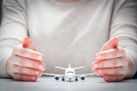 modelo de avión rodeado de manos en gesto de protección. Concepto de la industria de la aviación, la seguridad aérea, la seguridad y el seguro. Foto de archivo