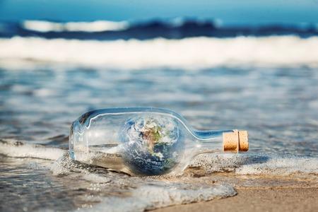 ecosistema: Tierra en la botella viene con la onda de océano. Concepto de medio ambiente, cuidado de la naturaleza, guardar el mensaje mundo limpio. Los elementos de esta imagen proporcionada por la NASA
