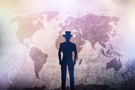 adventure: Silhouette of a man in hat standing in front of world map on grunge concrete wall in colorful spotights. Concepts of travel, future plan, adventure