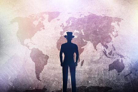 aventura: Silueta de un hombre en el sombrero que se coloca delante del mapa del mundo en el muro de cemento del grunge en spotights de colores. Los conceptos de viajes, plan de futuro, aventura