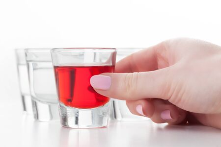 flavoured: Womans hand reaching for a glass of alcohol drink. White background.