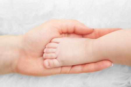 pie bebe: pie de bebé recién nacido en la mano de la madre. Concepto de cuidado de niños, la protección, el amor de los padres