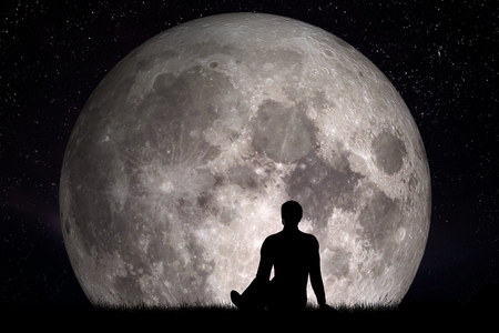 Man sitting alone on grass and looking on moon. Imagine the future concept. 3D rendering. Elements of this image furnished by NASA