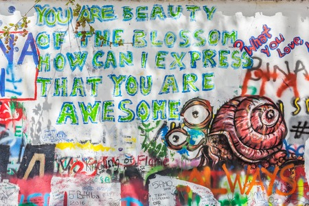 irritation: PRAGUE, CZECH REPUBLIC - APRIL 29, 2016: John Lennon Wall has been filled with Lennon inspired graffiti and lyrics from Beatles songs since the 1980s as irritation of the communist regime.