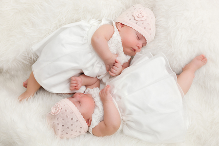 Nette Zwillingsschwestern, liegend Neugeborenen zusammen. Das Tragen elegante weiße Kleider