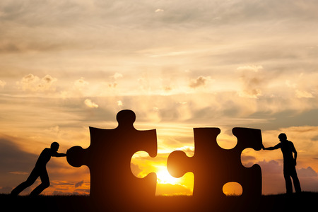 business puzzle: Two men connect two puzzle pieces. Sunset sky. Concept of business solution, teamwork, solving a problem, challenge