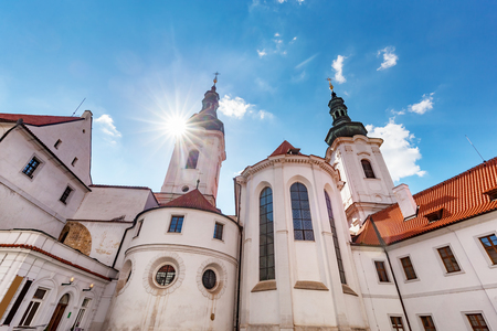 The Basilica of the Assumption of Our Lady in Strahov Monastery, Prague, Czech Republic. Sun shining on blue sky. Stock Photo