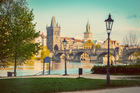 praha: Prague, Czech Republic skyline with historic Charles Bridge and Vltava river as seen from spring park. Vintage Stock Photo