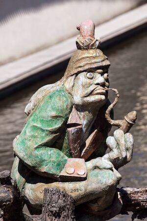 molino de agua: La estatua duende agua que guarda Velkoprerovsky molino, el molino de agua en corriente de Certovka o del diablo en la isla de Kampa, Praga, República Checa Foto de archivo