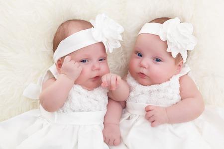 bebes recien nacidos: Hermanas gemelas bebés acostado juntos en blanco manta de piel suave. Usando elegantes vestidos blancos