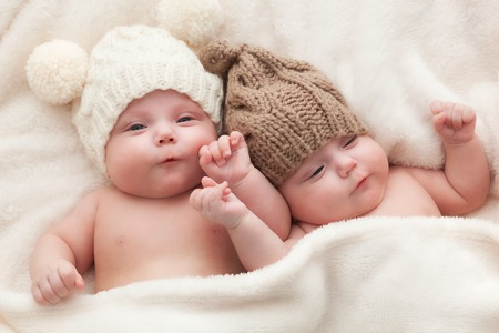 아기: Twin sisters babies lying together wearing funny woolen bobble hats. Happy childhood 스톡 콘텐츠