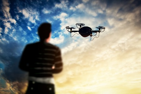 pilotage: Man operating a drone at sunset. Aerial videography job. 3D rendering Stock Photo