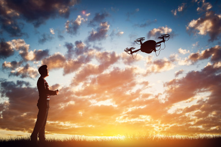 airscrew: Man operating a drone at sunset using a controller. 3D rendering