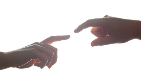 men and women: Mans and womans hands, fingers reaching each other. Soft, gentle gesture in strong backlight. Love, connect, help concepts. Stock Photo