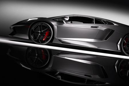 Grau schnellen Sportwagen im Scheinwerfer, schwarzer Hintergrund. Glänzend, neu, luxuus. 3D-Rendering