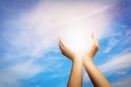 Raised hands catching sun on blue sky. Concept of spirituality, wellbeing, positive energy etc.