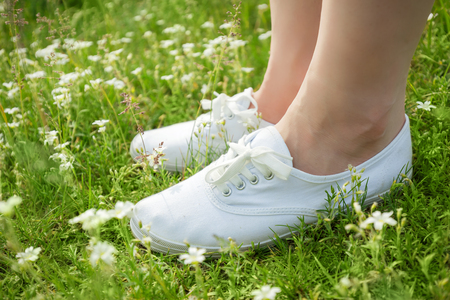 Young woman in white classic sneakers standing in grass on spring meadow with flowers. Legs close-up.