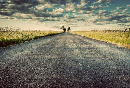 new direction: Empty straight long asphalt road. Dramatic cloudy sky. Concepts of travel, adventure, destination, transport etc. Vintage style