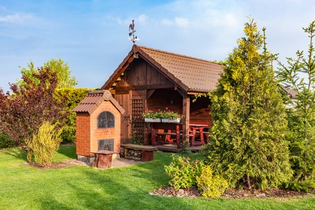 flowerbeds: Landscaped summer garden with barbecue and wooden summerhouse. Green trees, flowerbeds, mown grass.