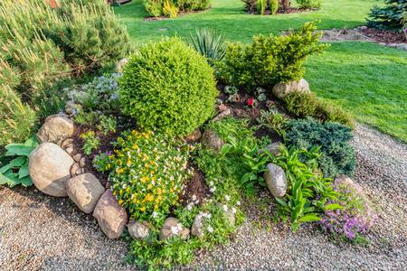 Gepflegt Sommergarten mit grünen Pflanzen, Felsen, vaus Blumen in Blumenbeeten, gemähtem Gras.
