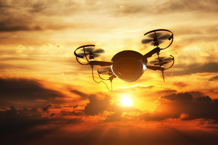 airscrew: Drone flying at sunset. Sun shining on dramatic sky. 3D rendering Stock Photo