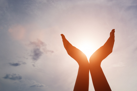 Raised hands catching sun on sunset sky. Concept of spirituality, wellbeing, positive energy etc. Stock Photo