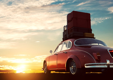 Coche rojo retro con el equipaje en las barras de techo al atardecer. Viajes, conceptos de vacaciones. ilustración 3D Foto de archivo - 64702967