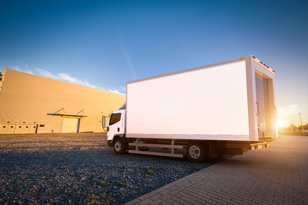 Commercial delivery truck with blank white trailer on cargo parking. Generic, brandless vehicle design. 3D rendering
