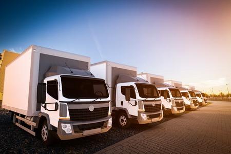 Vloot van commerciële vrachtwagens op cargo parkeren. Generieke, merkloze ontwerp van voertuigen. 3D-rendering