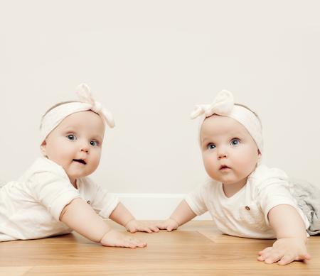 cintillos: hermanas gemelas bebé lindo arrastran juntos en el piso de madera que llevaba cintas para la cabeza divertido. Vendimia