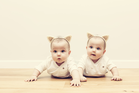 cintillos: hermanas gemelas bebé lindo arrastran juntos en el piso de madera con orejas de cintas para la cabeza del gato divertido. Vendimia